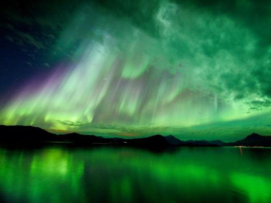 Aurora that appears to be casting rays of green sunlight through the clouds.  Image courtesy of Hugo Løhre