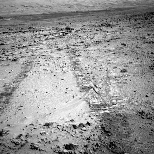 Curiosity snaps a picture of the marks made by its wheels as the one-ton rover heads toward Mount Sharp.  Credit: NASA/JPL-Caltech